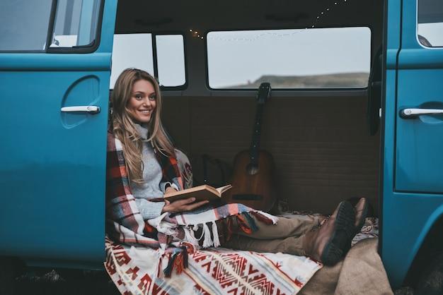 Herbstabenteuer. attraktive junge frau bedeckt mit decke, die ein buch liest und lächelt, während sie innerhalb des blauen retro-art-minivans sitzt