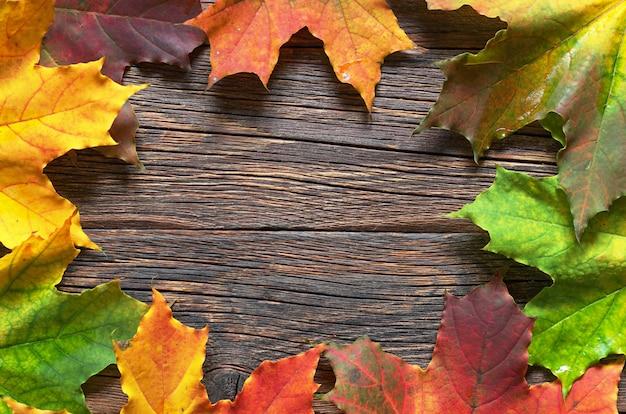 Herbstahornblätter auf altem hölzernen hintergrund