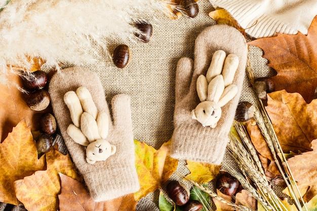 Herbstahornblätter, handschuhe mit kleinem teddybären und kastanien, die auf einem braun liegen.