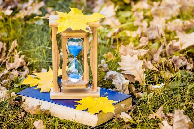 Herbstahornblätter liegen auf einer sanduhr und einem buch im wald