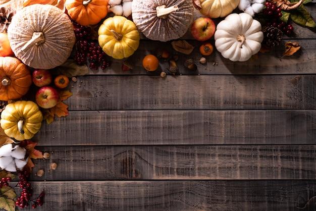 Herbstahornblätter mit kürbis auf hölzernem hintergrund. thanksgiving-konzept.