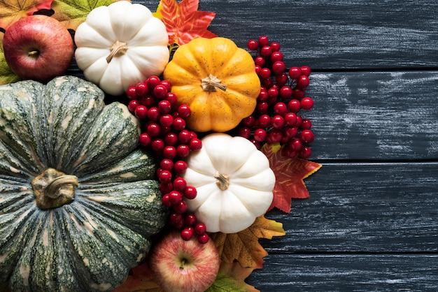 Herbstahornblätter mit kürbis und roten beeren auf altem hölzernem. erntedankfest-konzept.
