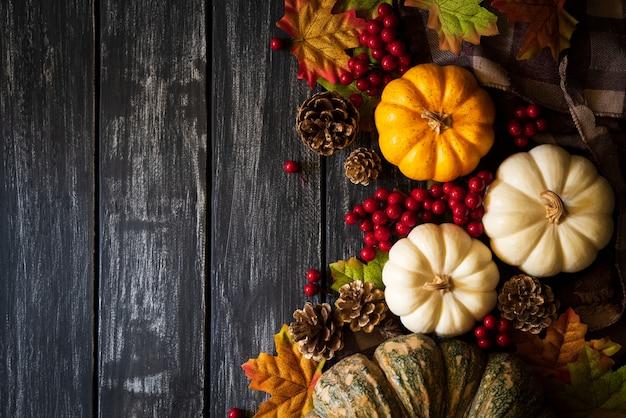 Herbstahornblätter mit kürbis und roten beeren auf altem hölzernem. thanksgiving-konzept.