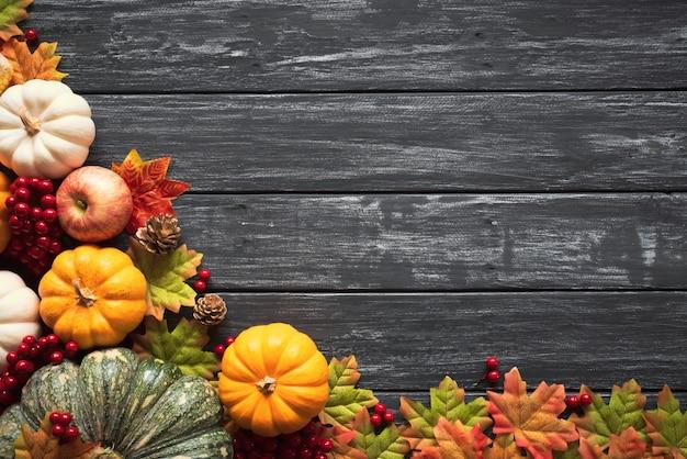Herbstahornblätter mit kürbis und roten beeren auf altem hölzernem.