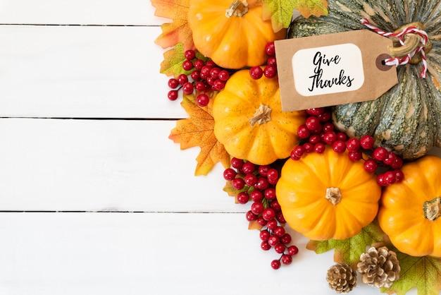 Herbstahornblätter mit kürbis und roten beeren auf hölzernem hintergrund. erntedankfest