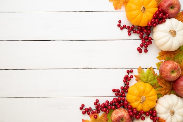 Herbstahornblätter mit kürbis und roten beeren auf weißem hölzernem. erntedankfest-konzept