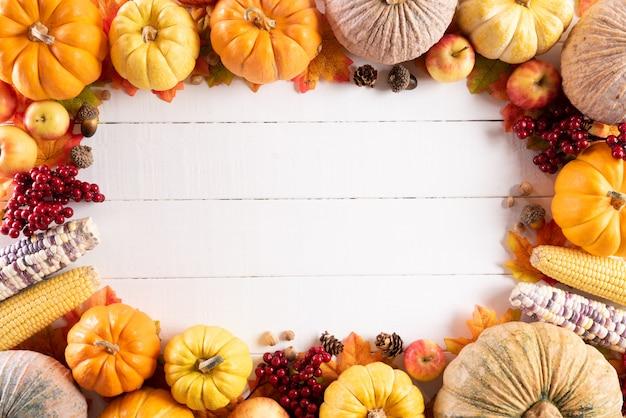 Herbstahornblätter mit kürbis und roten beeren, erntedankfestkonzept.