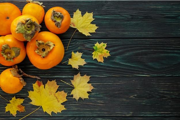 Herbstahornblätter und reife persimonen auf einem strukturierten hölzernen hintergrund