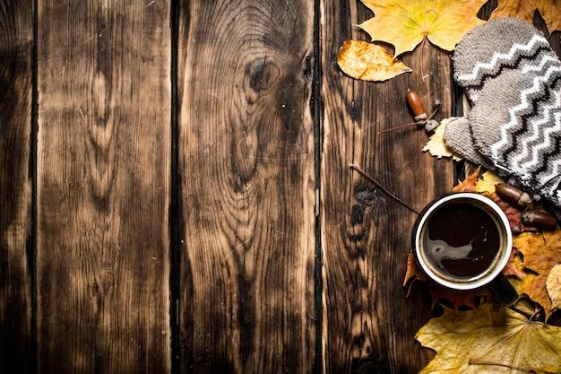 Herbstart eine tasse heißen kaffee mit handschuhen auf einem holztisch
