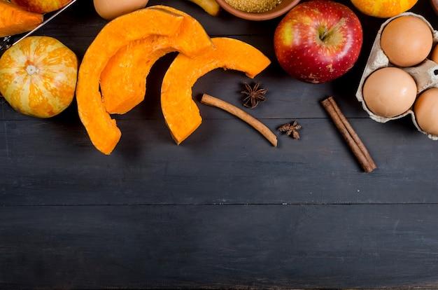 Herbstbackkonzept. rahmen mit kürbis, apfel, nüssen, zimt, ei und mehl auf dem holztisch. kochen backprozess mit zutaten. ansicht von oben. platz kopieren,