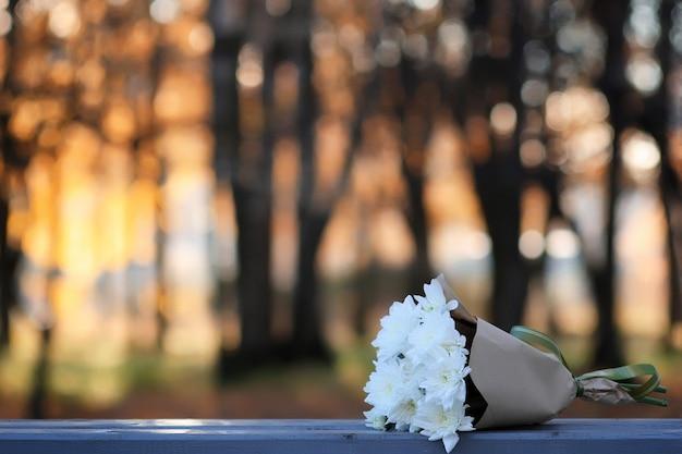 Herbstbank in einem park verloren blumenstrauß
