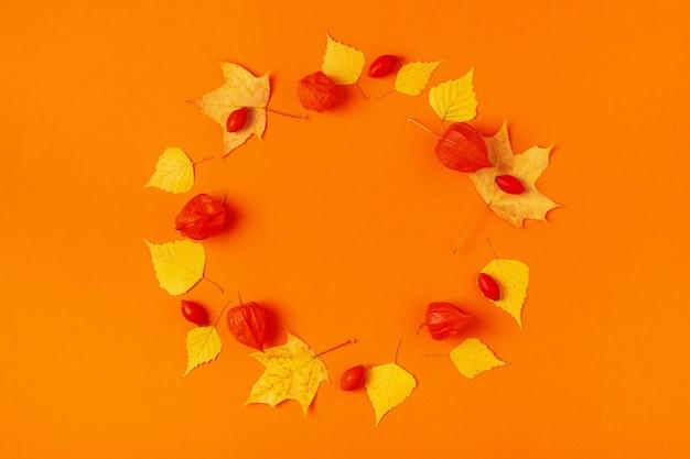 Herbstblätter auf einem orangefarbenen hintergrund