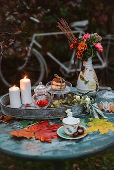 Herbstblätter liegen auf einem antiken runden holztisch mit geschirrbechern und keksen, die kerze brennen.