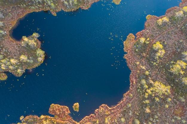 Herbstblauer see mit inseln im wald, luftaufnahme durch drohne