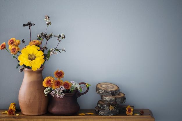 Herbstblumen in rustikaler keramikvase auf grauer hintergrundwand