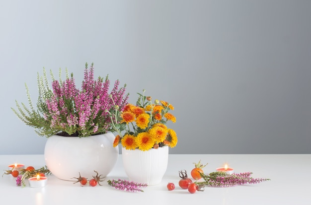 Herbstblumen mit brennenden kerzen auf weißem tisch