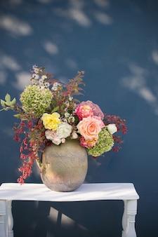 Herbstblumen und beeren in rustikalem keramikkrug auf blauer hintergrundwand
