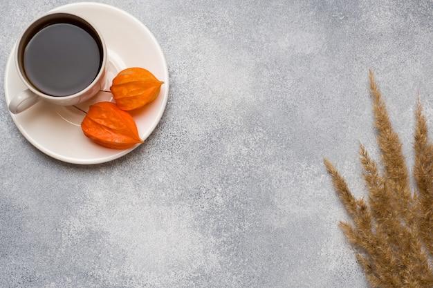 Herbstblumen und ein tasse kaffee auf dem tisch mit einer kopie des raumes.