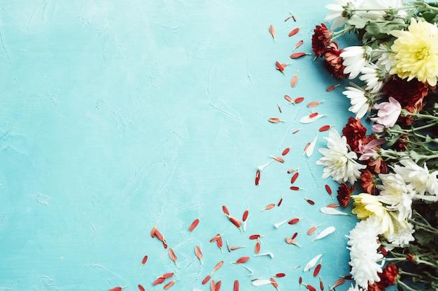 Herbstblumenmischung auf einer blauen wand. zartes blütenblattkonzept