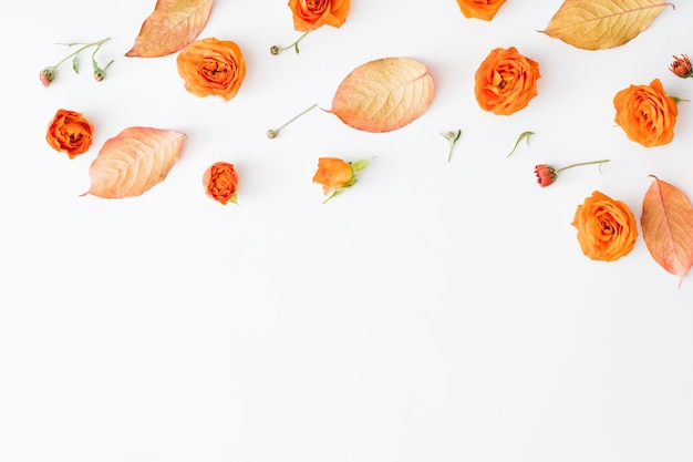 Herbstblumenmuster abstrakt rote blätter und offene orangefarbene rosenknospen auf weißer oberfläche verstreut