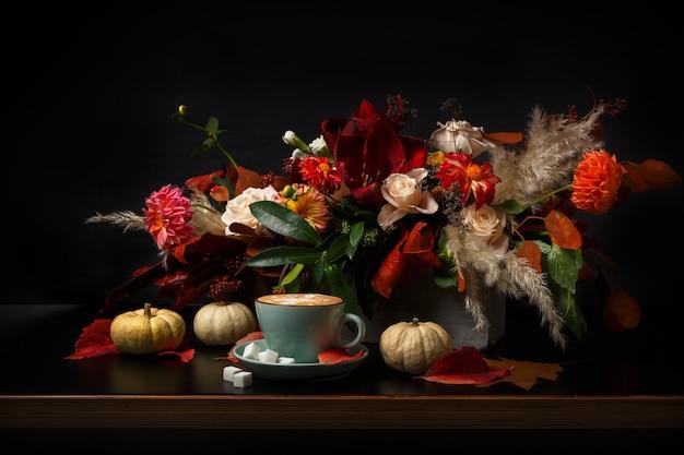 Herbstblumenstrauß. bunte und warme herbstkomposition mit cappuccino, kürbisse auf holztisch. urlaubs- und blumenmusterkonzept