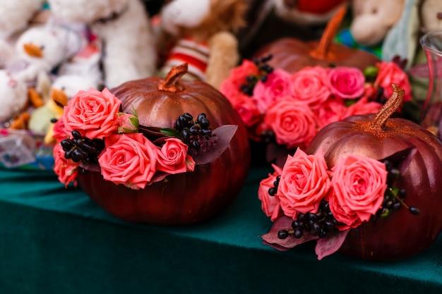 Herbstblumenstrauß im goldenen kürbis, halloween-inspiration.