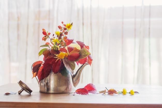 Herbstblumenstrauß in eiserner teekanne auf holztisch
