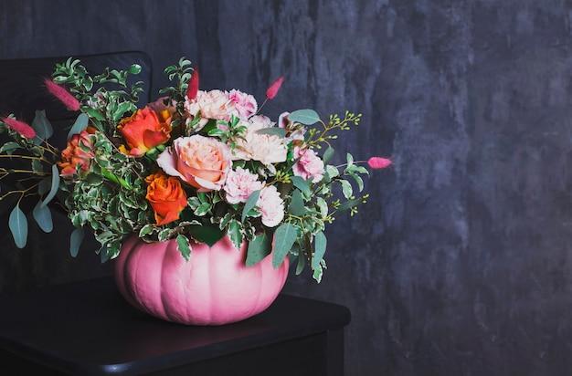 Herbstblumenstrauß in farbigem kürbisvase auf schwarzem stuhl, co