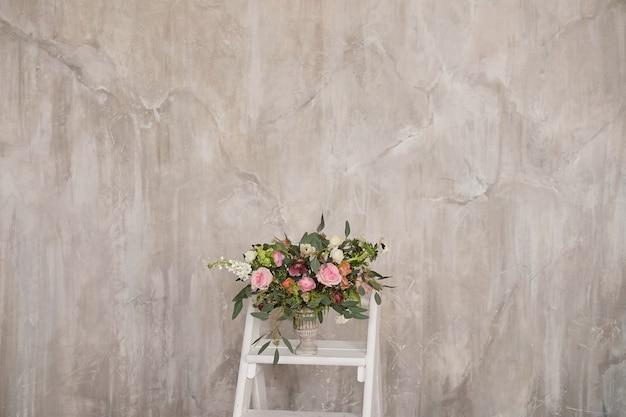 Herbstbrautblumenstrauß von blumen steht an auf der seitenansicht der weißen treppenhaustrittleiter
