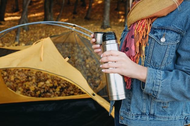 Herbstcamping. beschnittener schuss der dame mit vakuumflasche im herbstnaturpark.