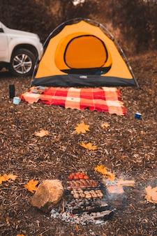 Herbstcampingplatz mit lagerfeuerzelt und auto auf hintergrundkopierraum