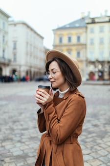 Herbstdame, die kaffee auf herbststadt trinkt