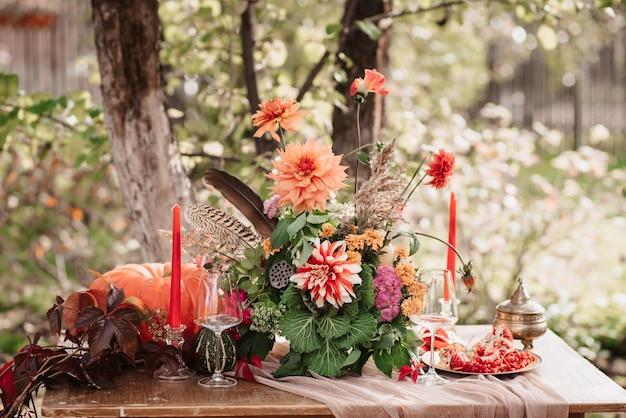 Herbstdekor: ein strauß dahlien, granatäpfel, kerzen, kürbisse und gläser