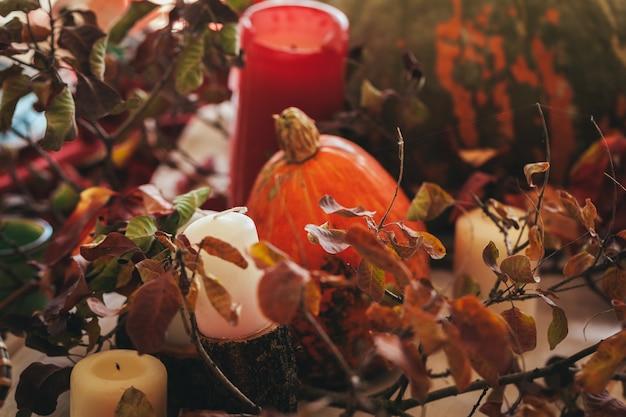 Herbstdekor mit kürbis, kerzen und geschirr