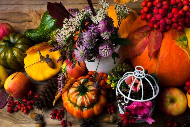Herbstdekor mit vogelkäfig, äpfeln und blumen