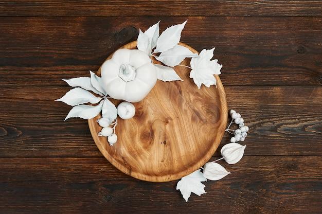 Herbstdekor mit weißblättern und kürbis mit hölzernem platz auf dunkelbraunem hölzernem backgound flachem lagemodell für ihren kunst-, bild- oder handbeschriftungszusammensetzungs-kopienraum, draufsicht