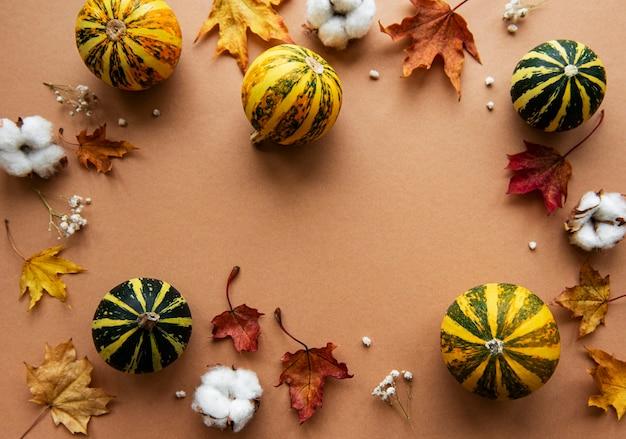 Herbstdekoration mit kürbissen und trockenen ahornblättern auf einem braunen hintergrund