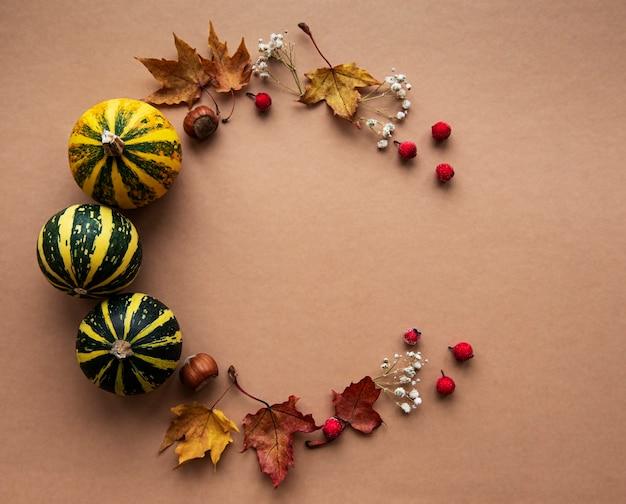 Herbstdekoration mit kürbissen und trockenen ahornblättern in form eines kreises auf einem braunen hintergrund
