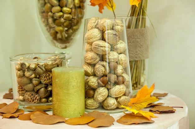 Herbstdekoration von nüssen aus gelben blättern und kerzen. herbstdekoration für den innenbereich handgefertigt