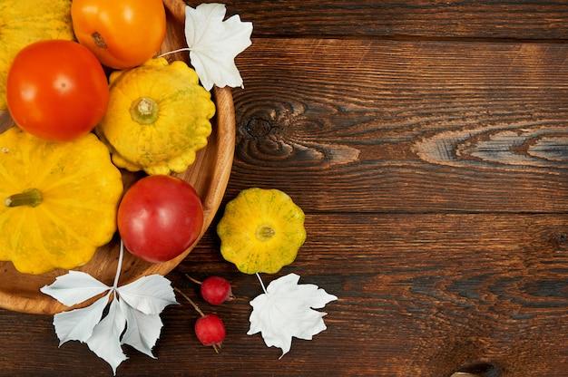 Herbstdekorrahmen mit kürbis und roter tomate auf dunkelbraunem holz