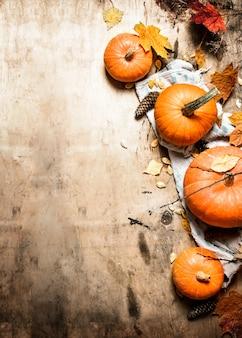 Herbsternte reifer kürbis mit blättern auf hölzernem hintergrund