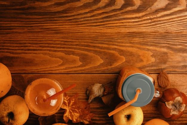 Herbsternte von kürbissen auf dem tisch reife kürbisse, äpfel, blätter und kaki auf holzh...