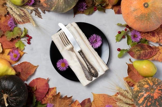 Herbsternterahmen mit kürbissen, birnen, blättern, blüten, viburnum, weizenähren und schwarzem teller in der mitte. sicht von oben