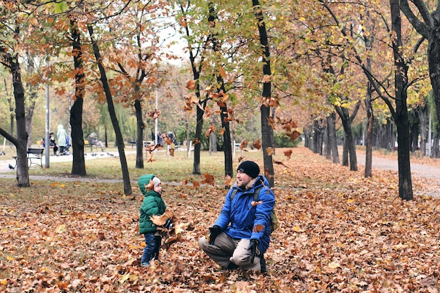Herbstfamilienspaziergang im wald. schöner park mit trockenen gelben blättern. sohn und vater, die händchen halten.