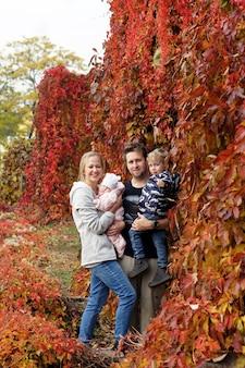 Herbstfamilienspaziergang im wald. schöner park mit trockenen gelben und roten blättern. mutter mit tochter und vater mit sohn und vater, die händchen halten.