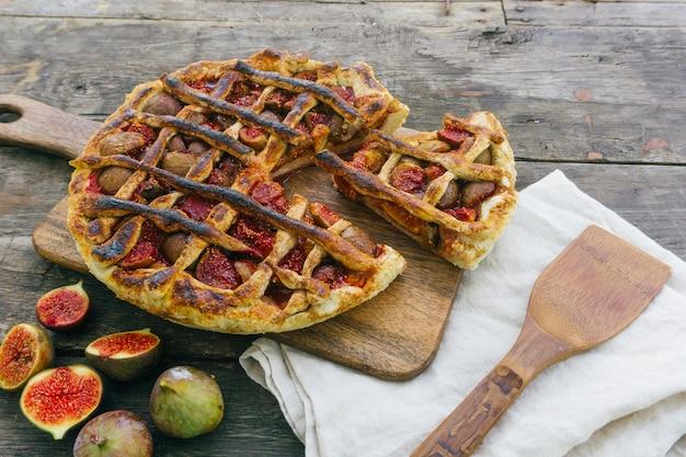 Herbstfeigenkuchen oder -törtchen mit zimt auf einem alten holztisch. ansicht von oben