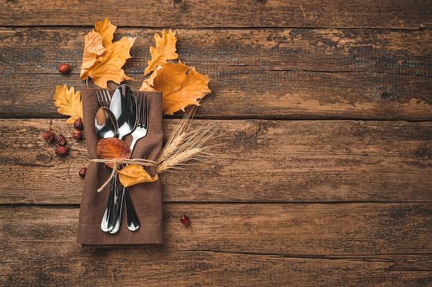 Herbstfestlicher kulinarischer hintergrund mit besteckserviette und herbstlaub auf einem hölzernen hintergrund