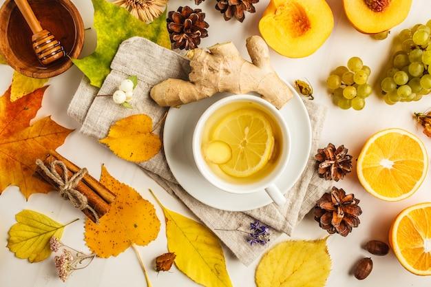 Herbstflachlage: tee, herbstfrüchte und dekorationen auf einem weißen hintergrund.
