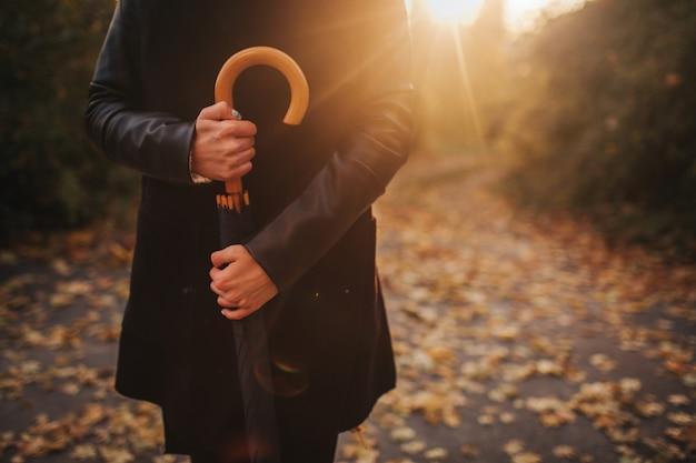 Herbstfrau im herbstpark mit schwarzem regenschirm