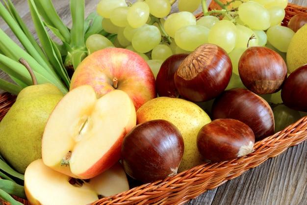 Herbstfrüchte mit rotem apfel in scheiben geschnitten und kastanien auf korb